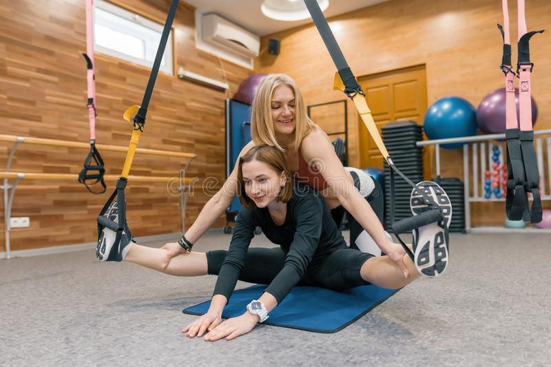 Female personal fitness instructor helping young girl to do exercises in gym on fitness loops straps. Sport, athlete, training, stock photo