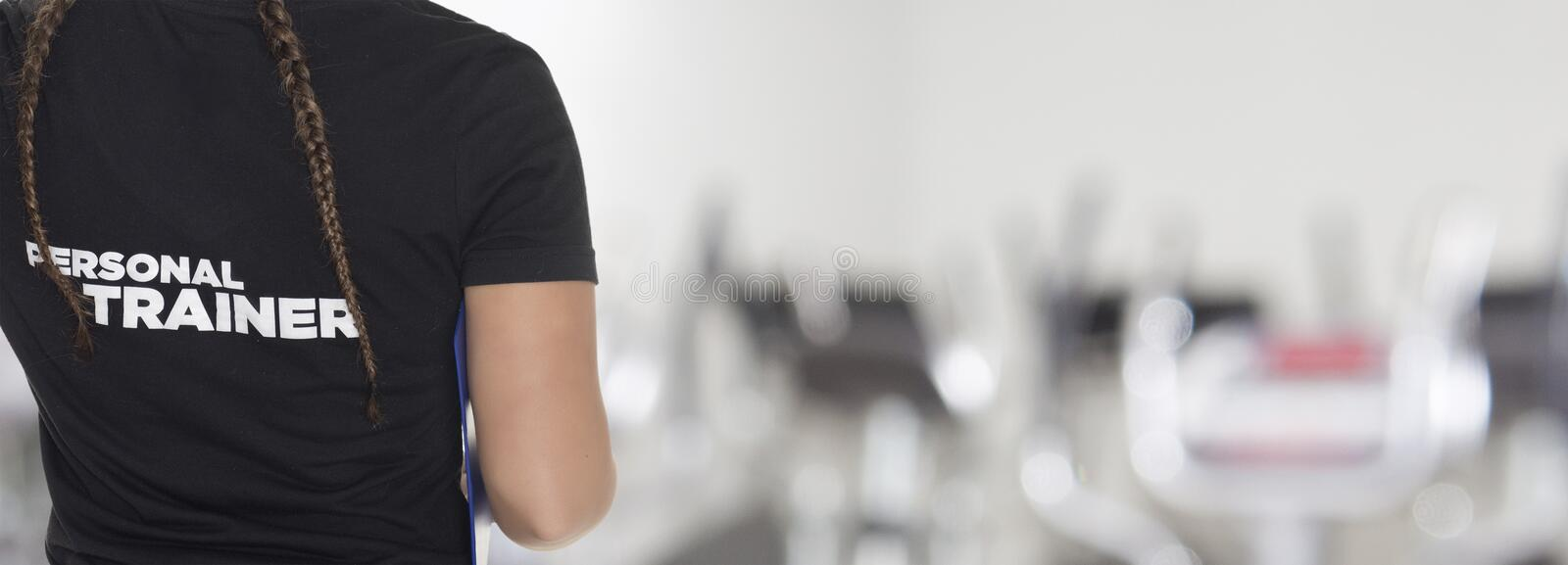 Female Personal Trainer. With his back facing the camera, looking at a gym royalty free stock photos