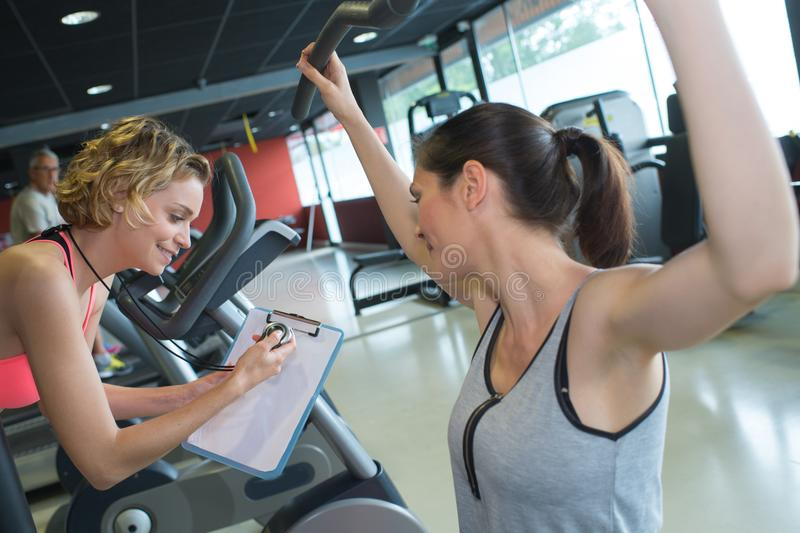 Female personal trainer helping woman in training. Female personal trainer helping women in training female royalty free stock photography