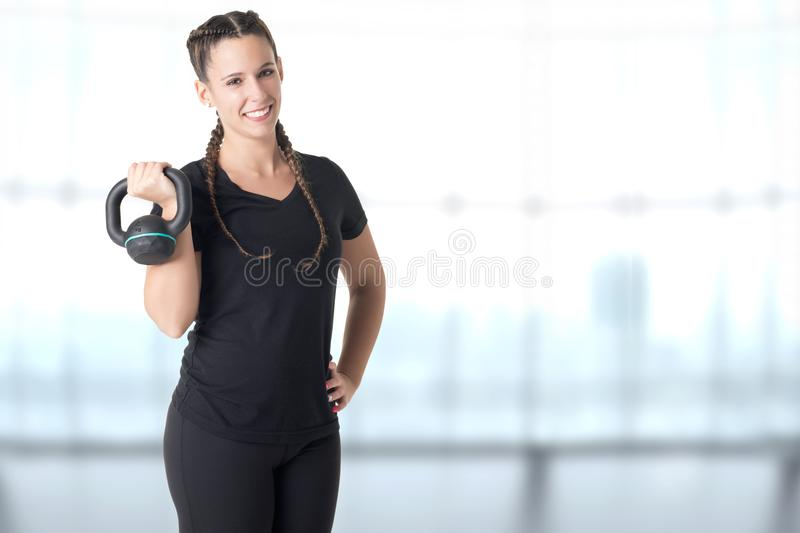 Female Personal Trainer. Holding a kettlebell, in a gym stock photography