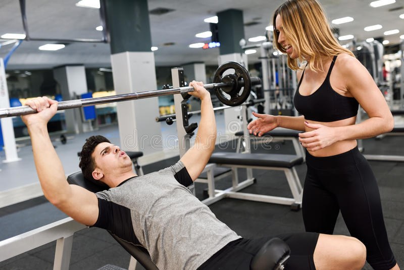 Female personal trainer motivating a young man lift weights. Female personal trainer motivating a young men lift weights while working out in a gym royalty free stock photo