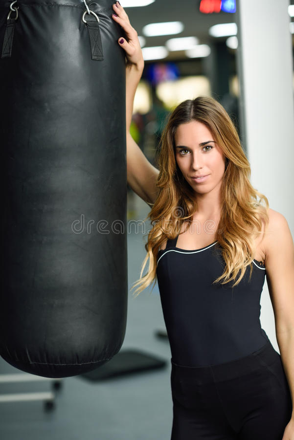 Female personal trainer with punching bag in a gym. Woman wearing sportswear clothes royalty free stock photo