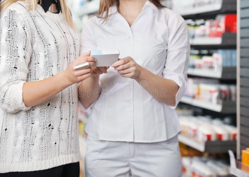 Female Pharmacist Advising Customer royalty free stock photography