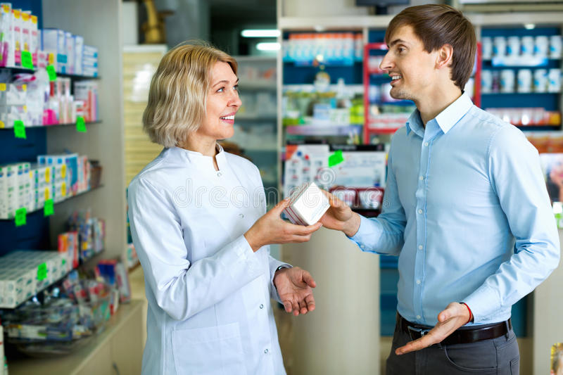 Female pharmacist counseling customer about drugs usage stock photo