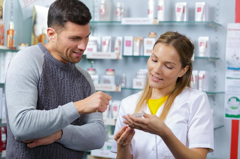 Female pharmacist counseling customer about drugs usage stock photos