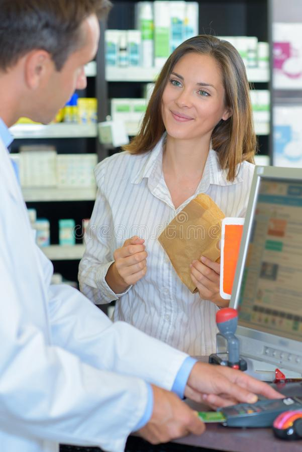 Female pharmacist counseling customer about drugs usage in modern farmacy. Male royalty free stock photography