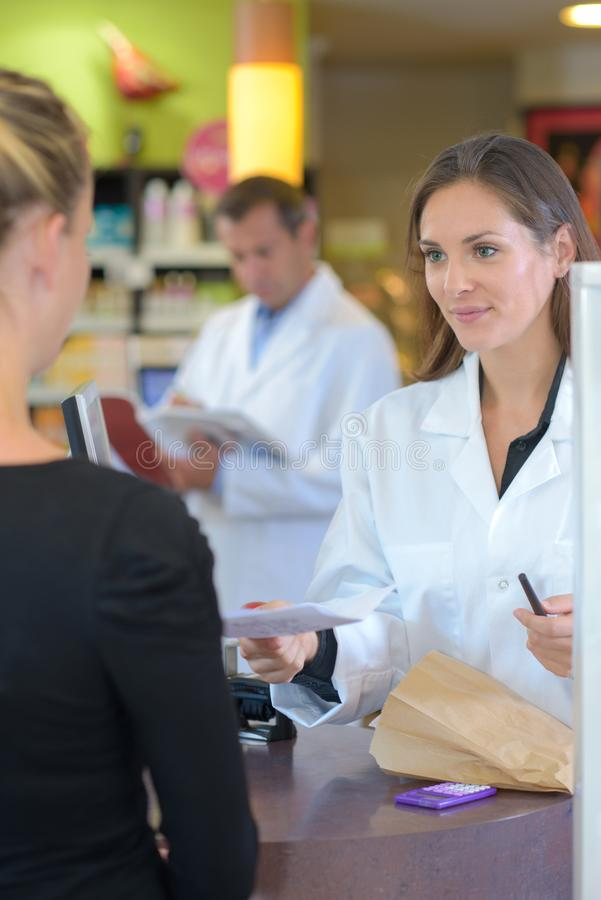 Female pharmacist counseling customer about drugs usage in modern farmacy royalty free stock photo