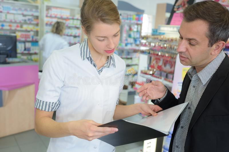 Female pharmacist counseling customer in modern farmacy. Female stock photography