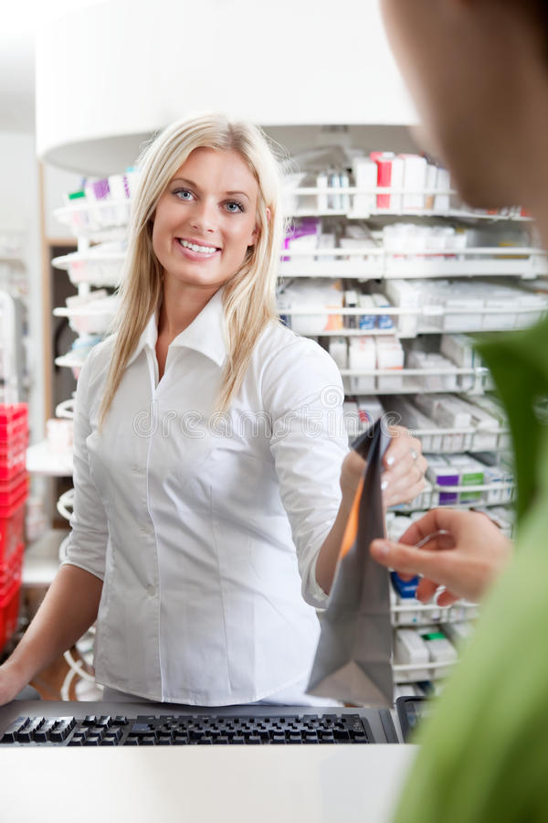 Female Pharmacist With A Customer In Pharmacy stock image