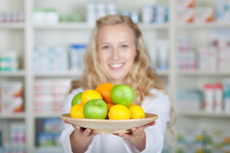 Female Pharmacist Holding Different Fruits stock photography