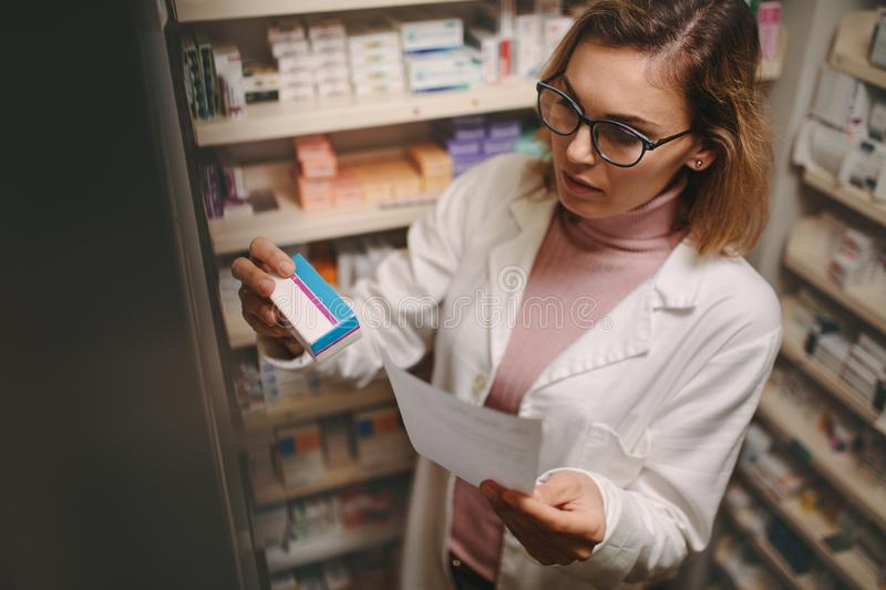 Female pharmacist with prescription checking medicine. Chemist with a prescription searching right medicine on shelves in pharmacy. Female pharmacist holding royalty free stock photography