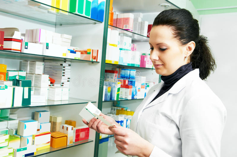 Female pharmacist with prescription in drugstore royalty free stock image