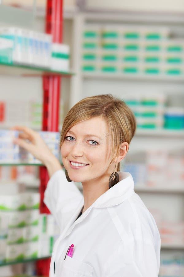 Female Pharmacist Selecting Medicine From Shelf royalty free stock photo