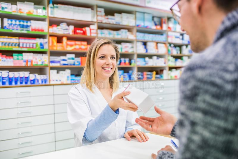 Female pharmacist serving a male customer. Female friendly pharmacist serving an unrecognizable male customer royalty free stock photo