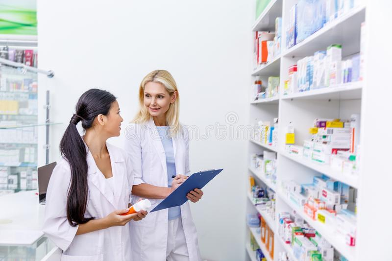Female pharmacists with medication and clipboard working together. In drugstore royalty free stock photos