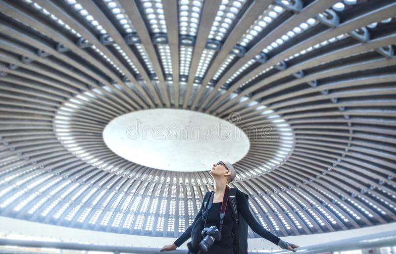 A female photographer admiring a huge circular concert hall ceiling stock images