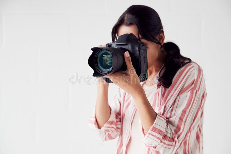 Female Photographer With Camera On Photo Shoot Against White Studio Backdrop stock photos