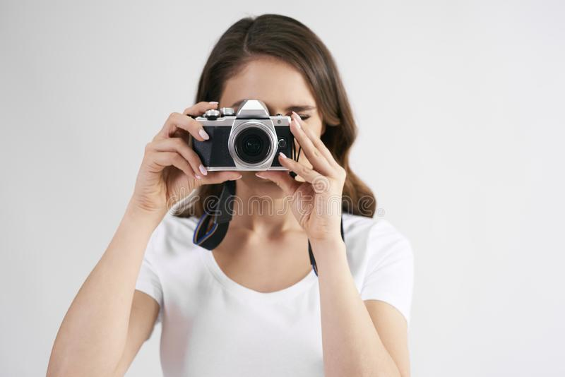 Female photographer with camera photographing in studio shot. Portrait of female photographer with camera photographing in studio shot stock images