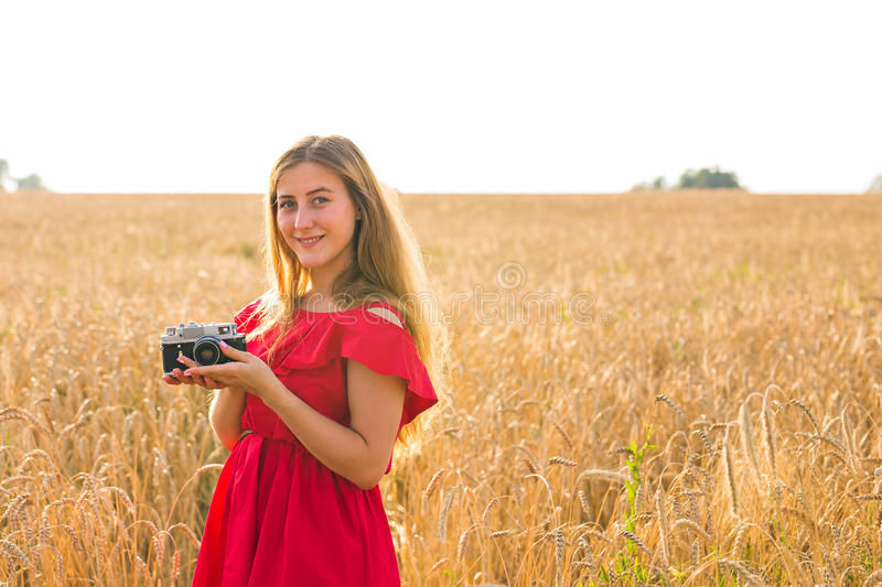 Female photographer in the field with a camera taking pictures.  stock photo