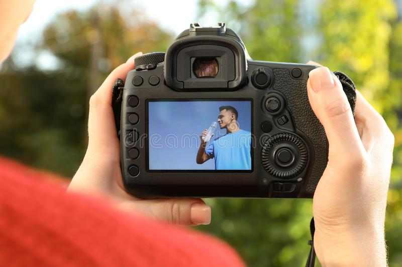 Female photographer holding professional camera with picture on screen outdoors royalty free stock photography