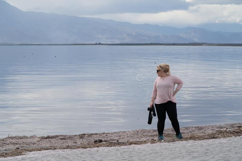 Female photographer stands on the shoreline of the Salton Sea, with her camera, staring off into the distance. Girl is wearing stock photography
