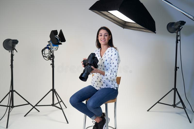 Portrait Of Female Photographer In Studio For Photo Shoot With Camera And Lighting Equipment. Female Photographer In Studio For Photo Shoot With Camera And stock photography