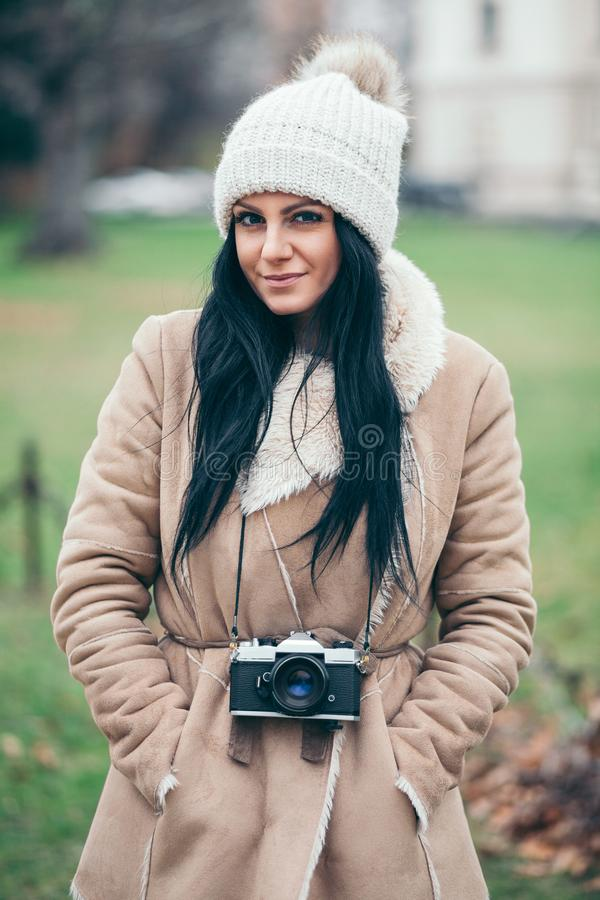 Female photographer taking pictures outdoors with a vintage camera royalty free stock image