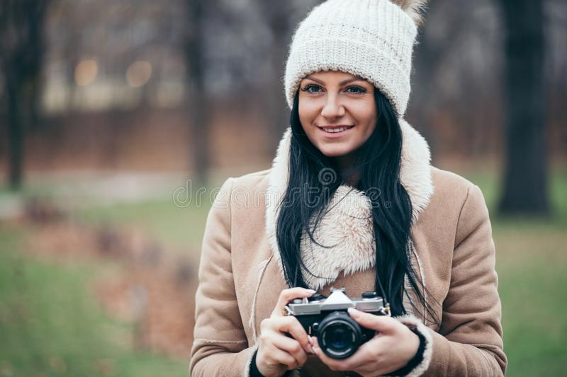 Female photographer taking pictures outdoors with a vintage camera royalty free stock photography