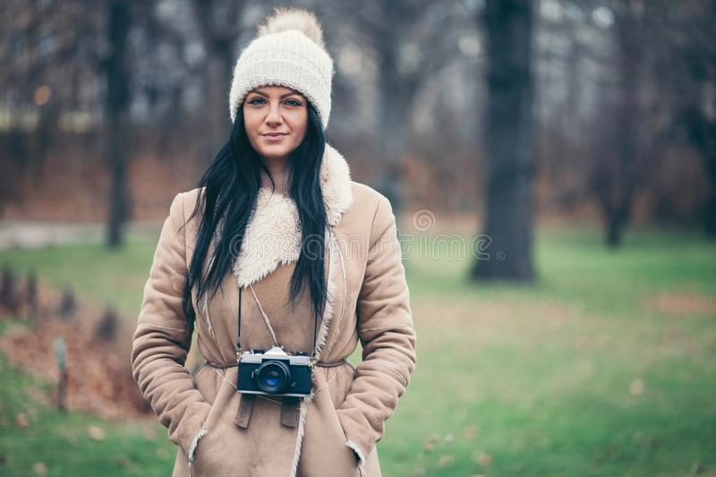 Female photographer taking pictures outdoors with a vintage camera royalty free stock photo