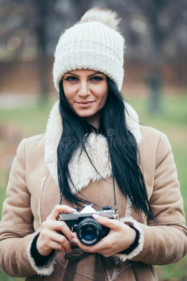 Female photographer taking pictures outdoors with a vintage camera stock image