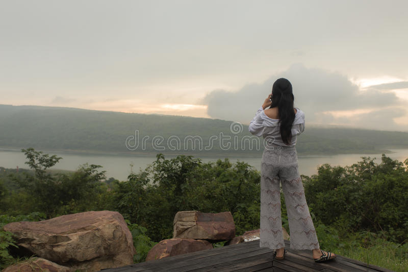 Female photographer taking pictures of the sunset. stock photography