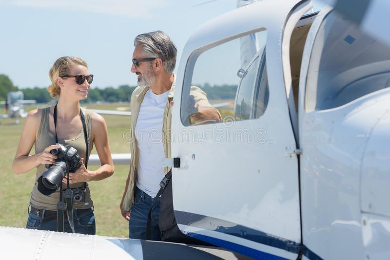 Female photographer talking to man exiting private jet. Female photographer talking to men exiting private jet man royalty free stock photos