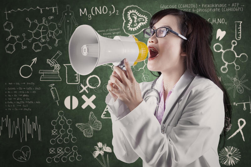 Female physician annoucing news. In front of medical symbols stock photography