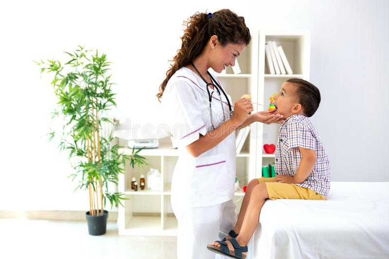 Female physician checking throat of a child stock photos