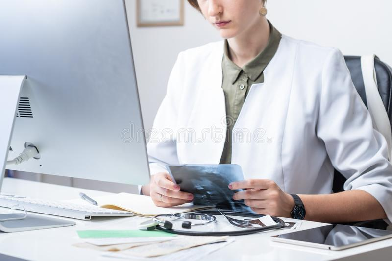 Female physician at modern medical doctor office. Woman examining x-ray at workplace in front of a desktop computer stock photo