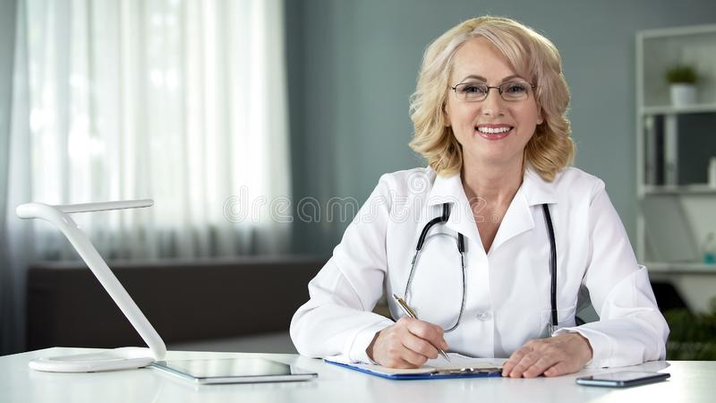Female physician sitting at table, smiling in camera, working medical records stock photo