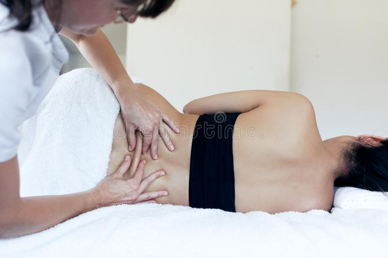 Female physiotherapist cures back pain of a pregnant woman in spa center. Shot of female physiotherapist cures back pain of a pregnant woman in spa center stock photos