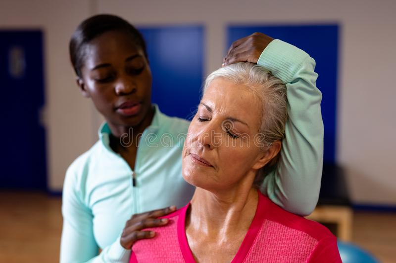 Female physiotherapist giving neck massage to active senior woman in sports center. Close-up of female physiotherapist giving neck massage to active senior woman stock images