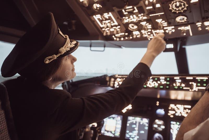 Female pilot captain prepares for take-off plane. Female pilot the captain of the plane prepares for take-off in the plane cockpit. Girl pilot in uniform flying stock images