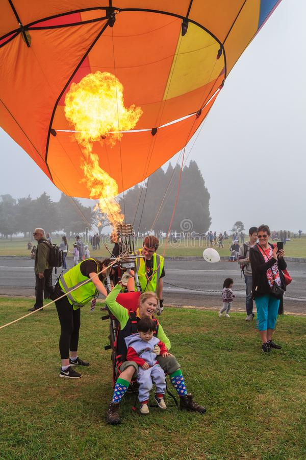 Woman demonstrating a single-seat hot air balloon to child. A female pilot in a `Chariot` single seat hot air balloon rig. She has an infant in her lap and is royalty free stock photos