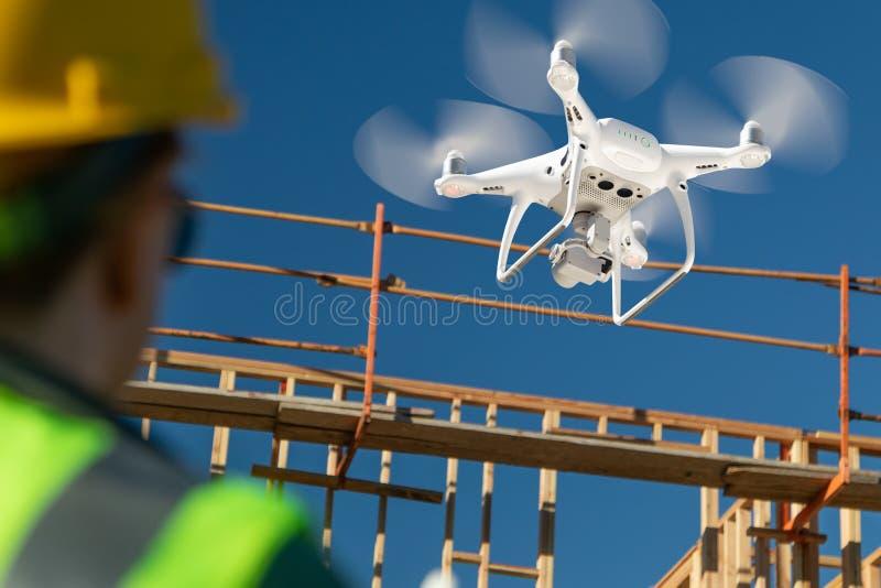 Female Pilot Flies Drone Quadcopter Inspecting Construction Site stock image
