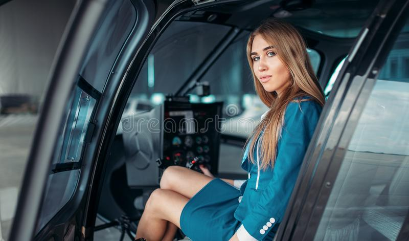 Female pilot in helicopter, view from windshield. Female pilot in headphones sits in helicopter. Air hostess in uniform in copter. Private airline royalty free stock photos