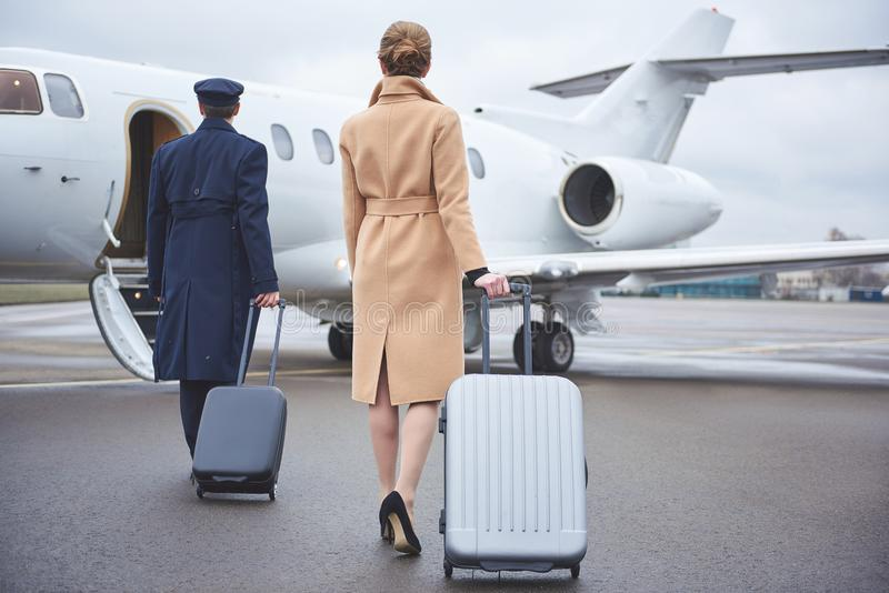 Female and pilot moving to aircraft. Full length girl and aviator keeping luggages while going to plain. They turning back to camera. Journey concept royalty free stock photography