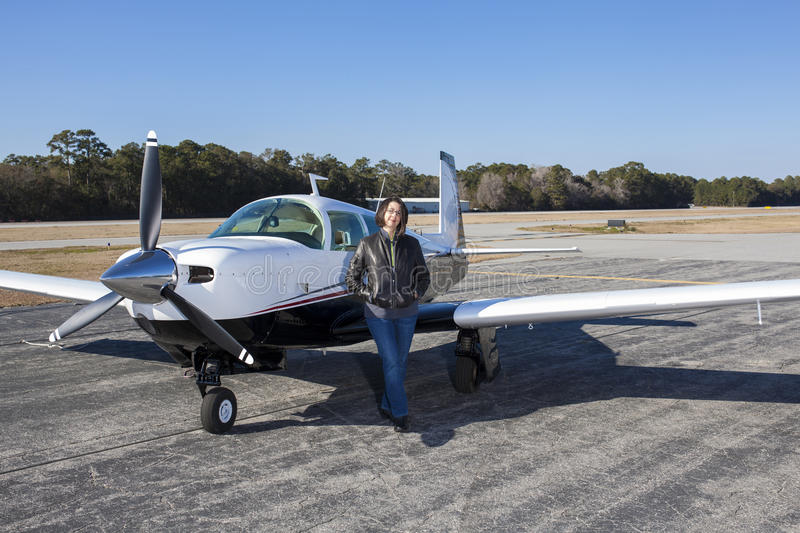 Female pilot with private plane. On tarmac stock image