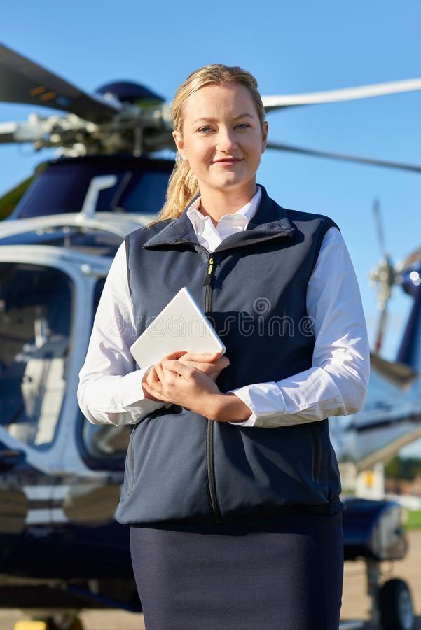 Portrait Of Female Pilot Standing In Front Of Helicopter With Di royalty free stock image