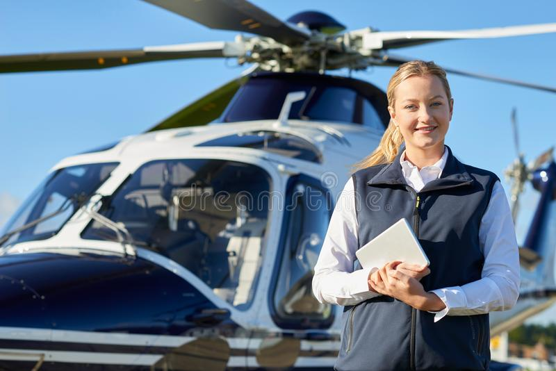Portrait Of Female Pilot Standing In Front Of Helicopter With Di stock photo