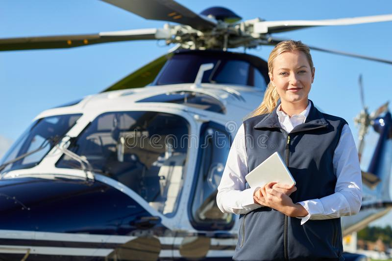 Portrait Of Female Pilot Standing In Front Of Helicopter With Di stock photography