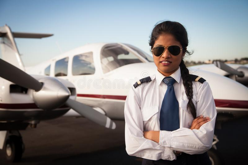 Female Pilot Waiting in Front of Her Aircraft. Waist up shot of a female pilot. She is dressed in uniform and standing in front of her aircraft stock photos