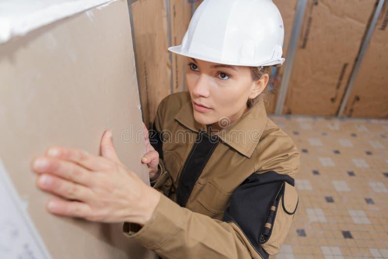 Female plasterer installing material on wall stock photos