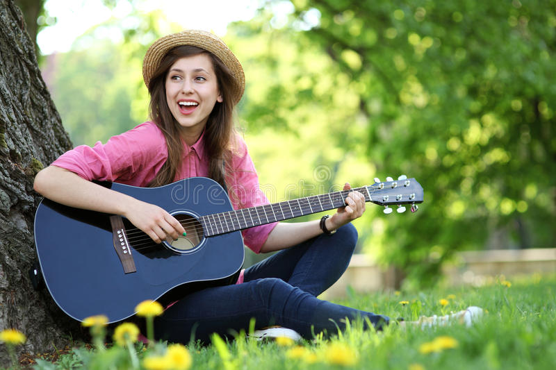 Female Playing Guitar In Park Stock Photo